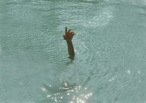 A person stretching a hand out of the water, possibly drowning